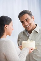 Hispanic woman giving husband birthday cake