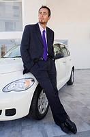 Hispanic car salesman leaning on new car