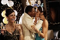 Multi-ethnic couple kissing at New Year's Eve party