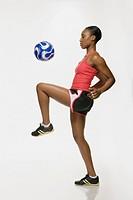 African American woman bouncing soccer ball