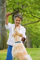 African American woman playing with dog (thumbnail)