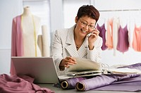 Asian female clothing designer talking on cell phone (thumbnail)