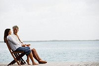 South American couple sitting on dock