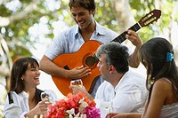 South American man playing guitar for friends