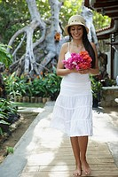 South American woman carrying bouquet of flowers