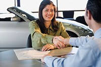 Woman shaking hands with car salesman (thumbnail)