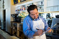 Hispanic cafe owner placing telephone order