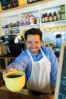Hispanic cafe owner handing coffee over counter