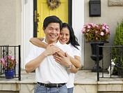 Asian couple hugging in front of house