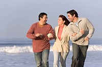 Hispanic friends walking on beach
