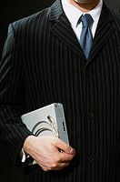 Businessman carrying an external hard drive