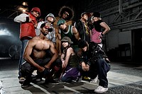 Multi-ethnic breakdancers posing in warehouse