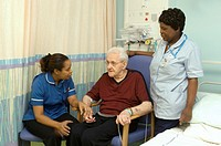 Patient care  Nurses talking with an elderly male patient on a hospital ward