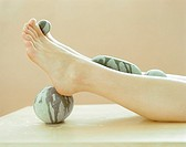 Stone therapy for legs and feet  The stones are heated and placed on various areas of the body to relax the muscles and ease pain