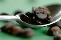 Roasted coffee beans on spoon, close-up