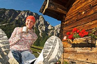 Woman in front of alpine hut, holding mug
