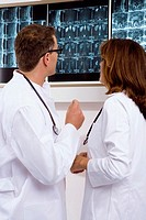 Male doctor and a female doctor examining an x-ray report