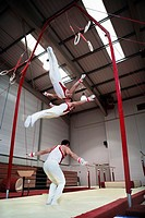 Gymnast performing on rings  Composite high-speed photograph of a gymnast dismounting rings in a gymnasium  This effect was achieved by photographing ...