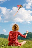 Woman sitting in mountain field Flying Kite back view (thumbnail)