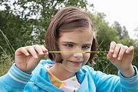 Girl 7_9 examining caterpillar on grass in field