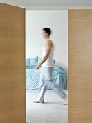 Man walking in bedroom side view blurred motion