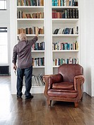 Middle_aged man taking book from shelf back view