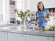 Mid_adult woman at kitchen sink preparing flowers to be put in vase
