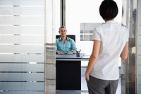 Man talking to woman standing in doorway of his office (thumbnail)