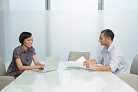 Man and woman working in conference room woman on laptop