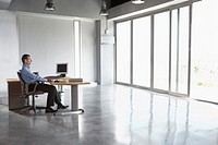 Man sitting at desk in empty office building