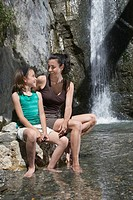 Mother and daughter 10_12 sitting on rock by river