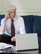 Business man using laptop sitting on sofa