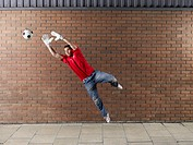 Goalkeeper reaching for football against brick wall