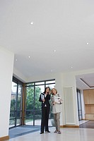 Real estate agent and woman observing new property