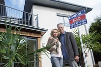 Couple embracing outside new home with sold sign portrait