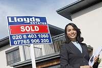 Real estate agent beside sold sign outside house portrait
