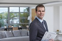 Male estate agent holding brochure in new home portrait
