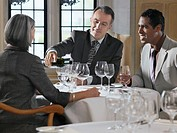 Three business people sitting at restaurant table man pouring wine
