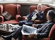 Two business men sitting in lobby talking one holding newspaper