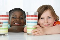 Two girls 5_6 leaning on table holding colourful glasses portrait close_up