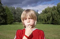 Portrait of boy 7_9 blowing whistle in meadow