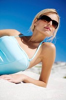 Young woman in swimming costume lying on the beach, sunglasses