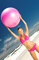 Young smiling woman in pink bikini on the beach, lifting a large ball