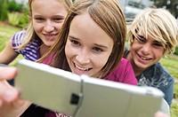 2 smiling teenage girls and boy using camera phone, outdoors