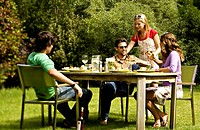 2 young couples sitting at garden table