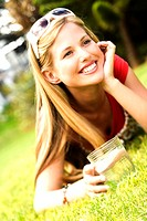 Young smiling woman lying on grass, glass of water