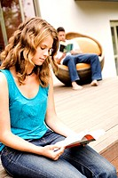 Young couple reading outdoors
