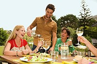 2 young smiling couples sitting at garden table, man pouring wine