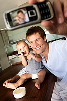 Father and son in kitchen, man taking a photograph of themselves, indoors