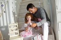 Father and ldaughter opening Christmas presents, girl holding a princess costume, indoors